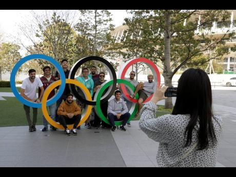 A group of students from Uruguay pose for a souvenir picture on the Olympic Rings set outside the Olympic Stadium in Tokyo, Saturday, March 21, 2020.