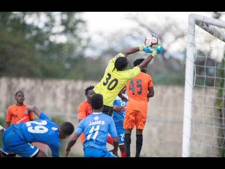 Tivoli Gardens' goalkeeper Davian Watkins (#30) punches a corner kick clear of the goal in their Red Stripe Premier League fixture against Portmore United at the Spanish Town Prison Oval on March 1, 2020.