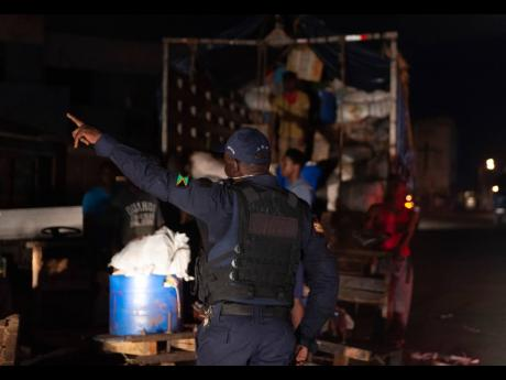 A member of the Jamaica Constabulary Force reprimands a group of men who were  unloading farm produce at the Coronation Market in downtown Kingston on Wednesday during the time of the islandwide curfew.