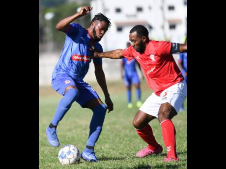 Action from the Red Stripe Premier League as Dunbeholden's Deandre Thomas (left) takes on UWI FC's Fabion McCarthy in a match at the UWI Mona Bowl on Sunday, January 12.