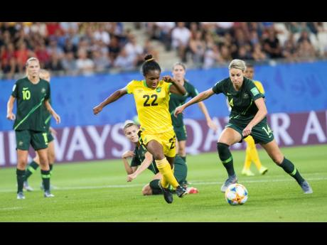 Jamaica's Mireya Grey (centre) on the attack while challenged by Australia's Alanna Kennedy (right) as Emily Van Egmond (left) looks on during their FIFA Women's World Cup match against Australia in Grenoble, France, on Tuesday, June 18, 2019.
