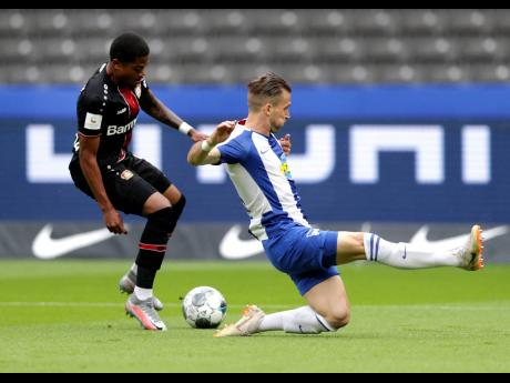 Bayer Leverkusen's Leon Bailey (left) challenges Hertha Berlin's Peter Pekarik for the ball during a German Bundesliga match in Berlin, Germany, on Saturday.