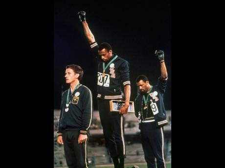In this file photo from October 1968, United States athletes Tommie Smith (center) and John Carlos (right) stare downward while extending gloved hands skyward during the playing of the American national anthem after Smith received the gold, and Carlos the bronze medal, for the men's 200m sprint at the Summer Olympic Games in Mexico City, Mexico. Australian silver medalist Peter Norman is at left. The Americans were using their international platform to protest for black civil rights back home.