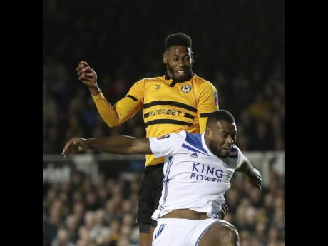 Newport County's Jamille Matt (top) scores his side's first goal of the game against Leicester City, during their English FA Cup third round match at the Rodney Parade stadium in Newport, England, Sunday, January 6, 2019.