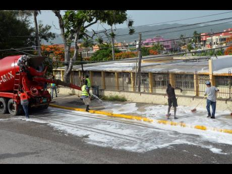 Sanitiser is being ejected from a truck on to a sidewalk along St James Street, while workers from the St James Municipal Corporation scrub the area, during a sanitisation exercise in Montego Bay on Sunday.