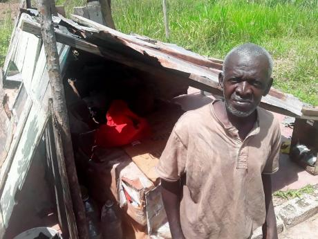 Leroy Andy in front of his 'home'. He is trying to build a better structure but cannot afford it.