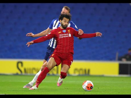Liverpool's Mohamed Salah (foreground) takes the ball away from Brighton's Dan Burn during the English Premier League match between Brighton and Liverpool at Falmer Stadium in Brighton, England, yesterday. Liverpool won 3-1.