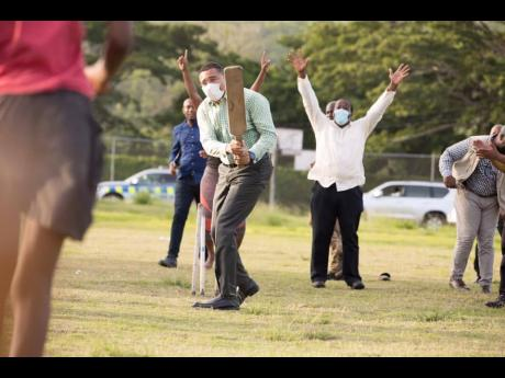 Prime Minister Andrew Holness shows off his flashing blade against members of a women's cricket team at Eden Park Sports Complex in St Mary last week.