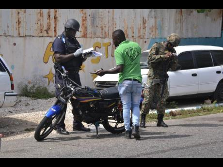 Members of the security forces conduct stop and search operations at the intersection of Charles and James streets in Kingston on Saturday.
