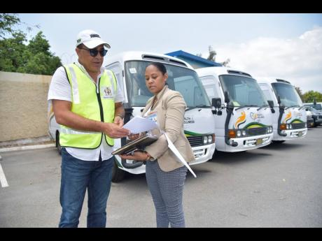 Minister of Health and Wellness, Dr  Christopher Tufton, looks at a document being shown to him by coordinator of medical technology services in the ministry, Mitchelle Maylor Archat.