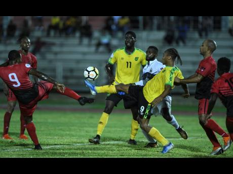 Jamaica's Bobby Reid controls the ball ahead of Antigua's Tevaughn Harriette in the Nations League match last year.