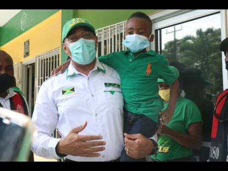Jamaica Labour Party leader Andrew Holness lifts up this little lad during his tour of Anchovy in South St James on Sunday.