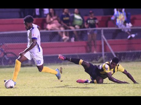 File Waterhouse's Kenroy Howell (left) slips away from a tackle from Jerome Odilon (right) from Don Bosco during a Concacaf club football match at the Anthony Spaulding Sports Complexon in  February 2, 2020.