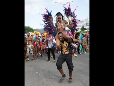 Daamar Levy carries his wife, Anecia, on his shoulders during Xaymaca International carnival road march last year.