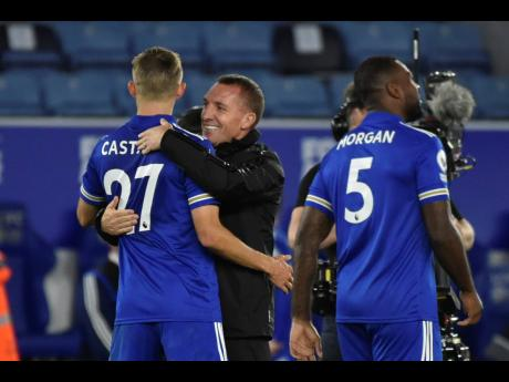 Leicester's head coach Brendan Rodgers (centre) embraces Leicester's Timothy Castagne after the English Premier League soccer match between Leicester City and Burnley at the King Power Stadium, Leicester, England, yesterday.