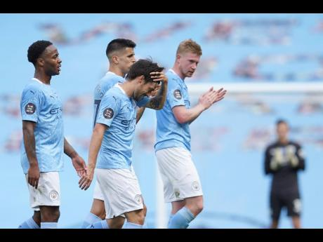 Manchester City's David Silva is applauded by team mates at the end of the English Premier League soccer match between Manchester City and Norwich City at the Etihad Stadium in Manchester, England, Sunday, July 26, 2020.