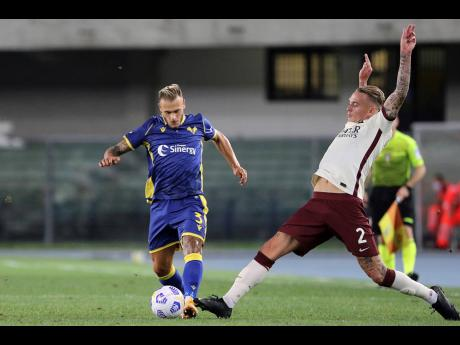 Verona's Federico Dimarco and Roma's Rick Karsdorp (right) compete for the ball during an Italian Serie A soccer match between Verona and Roma at the Bentegodi stadium in Verona, Italy, Saturday, September 19, 2020.