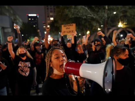 Protesters march on Thursday, in Louisville, Kentucky, USA. Authorities pleaded for calm while activists vowed to fight on in the state's largest city, where a gunman wounded two police officers during protests following the decision not to charge officers for killing Breonna Taylor.