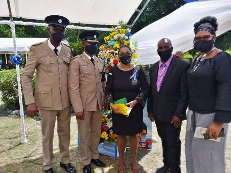Kemoy Wright (centre) is supported by (from left) Deputy Superintendent Owen Brown, Superintendent Christopher Phillips, retired inspector Lynoval Ruddock, and Blanche Codnor of the Police Federation.