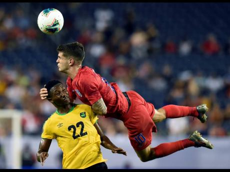 United States midfielder Christian Pulisic heads the ball above Jamaica midfielder Devon Williams during the second half of a Concacaf Gold Cup semi-final  match last year.
