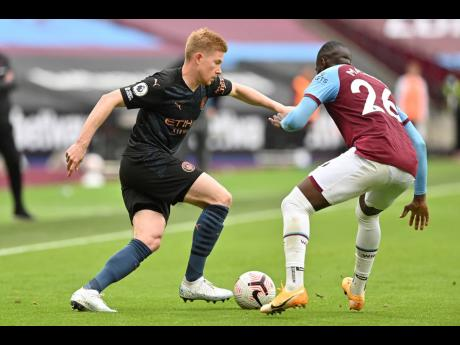 Manchester City's Kevin De Bruyne and West Ham's Arthur Masuaku (right) vie for the ball during their English Premier League match last Saturday.