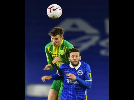 West Bromwich Albion's Conor Townsend, left, and Brighton's Adam Lallana challenge for the ball during the English Premier League  match between Brighton and West Bromwich Albion at the American Express Community Stadium in Brighton, England, yesterday.
