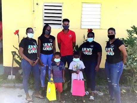 Petegay Gentles (second left) with members of the Army of Good making donations at the Mona Commons Basic School.