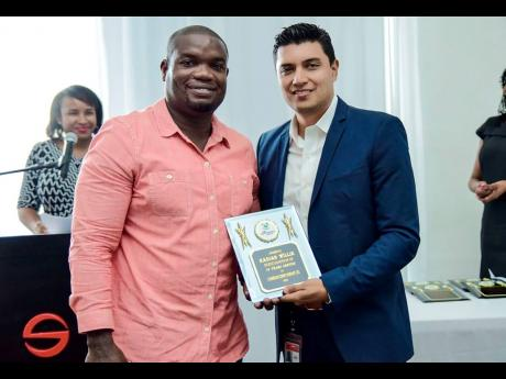 Kadian Willie (left) receives a plaque for long service from Jorge Camelo, human resources manager at Carib Cement.