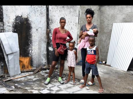 Peta-Gay Martin and members of her family, stands in the shell of their house that was destroyed by fire in May. The mother of six is seeking to have it rebuilt.