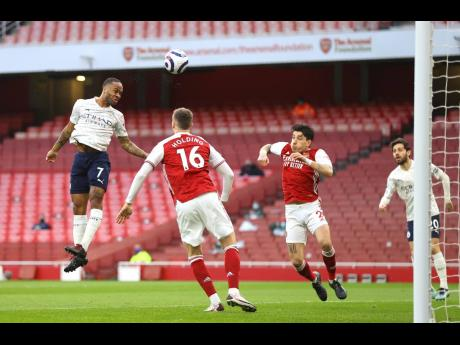 Manchester City's Raheem Sterling, left, scores his side's opening goal during the English Premier League match between Arsenal and Manchester City at the Emirates stadium in London, England, yesterday.