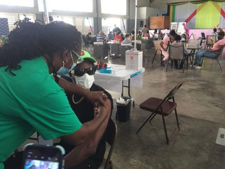Dancehall artiste Ding Dong getting vaccinated at the Girl Guides headquarters in St Andrew.