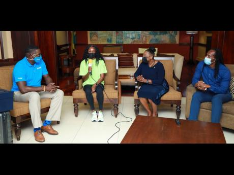Elaine Thompson-Herah, two-time double Olympic and 2021 Diamond League champion, addresses a welcome home press briefing on arrival at the Norman Manley International Airport's VIP Lounge. Also in the photo are Olivia Grange (second right), Minister of Culture, Gender, Entertainment and Sport; Alando Terrelonge (right), State Minister in the Ministry of Culture, Gender, Entertainment and Sport and Stephen Price, Vice President and general manager at Flow.