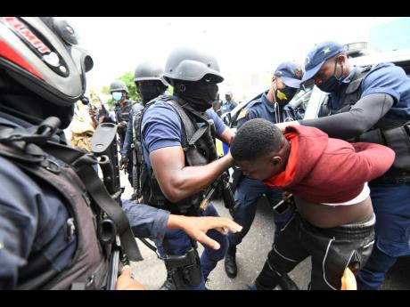Police arrest one of the demonstrators.