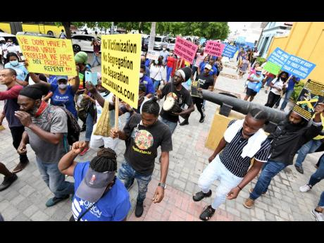 Persons protesting the 'vaccine mandate' in downtown Kingston make their way through downtown Kingston yesterday.